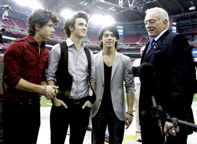 The Jonas brothers, from left, Nick Jonas, Kevin Jonas and Joe Jonas stand with Dallas Cowboys owner Jerry Jones al